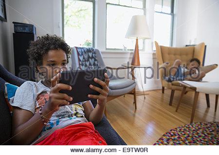 Brüder mit Technologie im Wohnzimmer - Stockfoto
