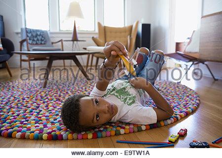 Jungen spielen mit Spielzeug Flugzeug auf Teppich - Stockfoto