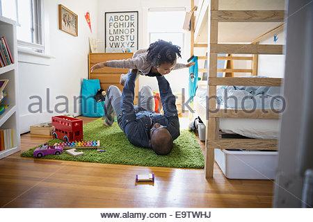 Vater heben fliegenden Tochter im Schlafzimmer - Stockfoto