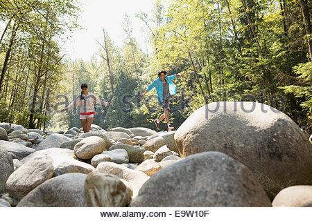 Freunde gehen auf Felsen im Wald - Stockfoto