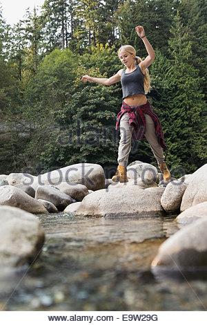Frau springen Felsen am Creekside in Wäldern - Stockfoto