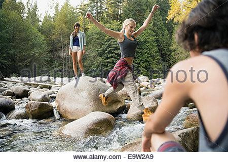 Freunde springen Felsen über Bach im Wald - Stockfoto