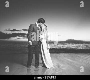 Schöne Hochzeitspaar, Braut und Bräutigam küssen am Strand bei Sonnenuntergang. Schwarz / weiß Foto - Stockfoto