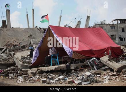 Gaza-Stadt, Gazastreifen, Palästinensische Gebiete. 3. November 2014. Palästinenser sitzen vor einem provisorischen Zelt errichtet in der Nähe von den Ruinen eines Hauses, das Zeugen sagten wurde zerstört durch israelischen Beschuss während des jüngsten Konflikts zwischen Israel und der Hamas, an einem regnerischen Tag im Osten von Gaza-Stadt 3. November 2014 Credit: Ashraf Amra/APA Bilder/ZUMA Draht/Alamy Live News