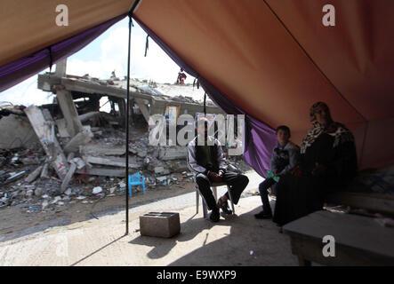 Gaza-Stadt, Gazastreifen, Palästinensische Gebiete. 3. November 2014. Palästinenser sitzen in behelfsmäßigen Zelt in der Nähe der Ruinen eines Hauses, das Zeugen sagten errichtet wurde zerstört durch israelischen Beschuss während des jüngsten Konflikts zwischen Israel und der Hamas, an einem regnerischen Tag im Osten von Gaza-Stadt 3. November 2014 Credit: Ashraf Amra/APA Bilder/ZUMA Draht/Alamy Live News