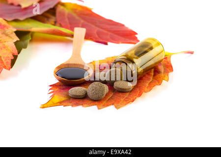 Medizin-Flasche, Pillen an Blatt und Sirup in einem Holzlöffel auf weißem Hintergrund - Stockfoto