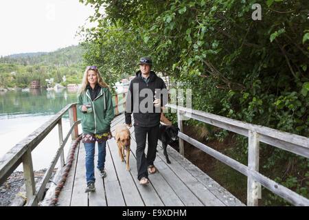 Paar Fuß mit ihrem Hund entlang der Promenade, Halibut Cove, Kachemak Bay, Yunan Alaska. - Stockfoto