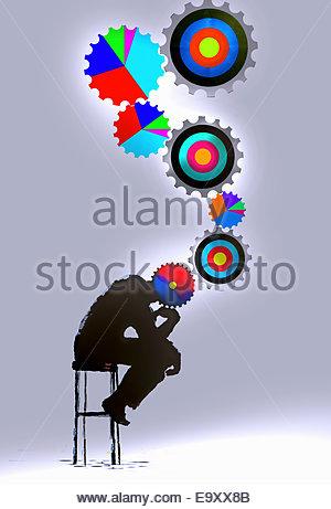 Der Denker mit angeschlossenen mehrfarbige Ziel- und Kreisdiagramm Zahnräder - Stockfoto