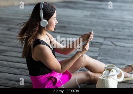 Eine junge Asiatin konsumieren von Inhalten auf ihr Smartphone im freien - Stockfoto
