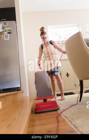 Junge Frau mit grünen Reinigungsmittel Staubsaugen - Stockfoto