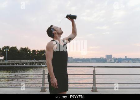 Junge männliche Läufer gießen Wasser über sein Gesicht am Ufer bei Sonnenaufgang - Stockfoto