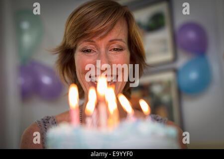 Reife Frau hält Geburtstagstorte mit Kerzen - Stockfoto