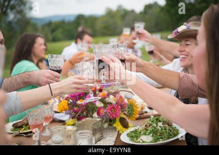 Familie und Freunde machen einen Toast auf Mahlzeit im freien - Stockfoto