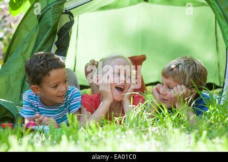 Drei Kinder liegen im Chat bei Gartenzelt - Stockfoto