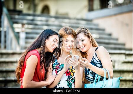Drei modische junge Frauen Blick auf Smartphone, Cagliari, Sardinien, Italien - Stockfoto