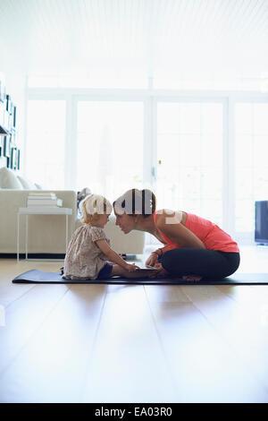 Mitte Erwachsene Mutter und Kleinkind Tochter üben Lotussitz im Wohnzimmer - Stockfoto