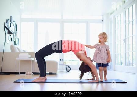 Mitte Erwachsene Mutter praktizieren Yoga mit neugierigen Kleinkind Tochter - Stockfoto