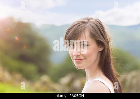 Porträt der jungen Frau lächelnd in sonniger Landschaft, Nahaufnahme - Stockfoto