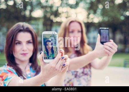 Zwei junge Freundinnen nehmen Selfie auf Smartphones im Einklang - Stockfoto