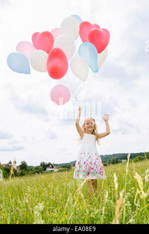 Mädchen halten Ballons im Feld - Stockfoto