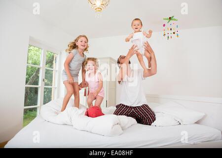 Vater, spielen mit Töchtern auf Bett - Stockfoto