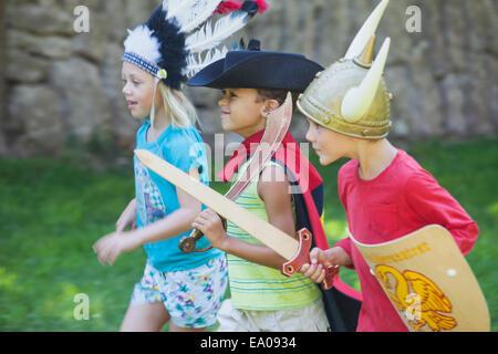 Drei Kinder tragen Fancy Dress Kostüme, spielen im park