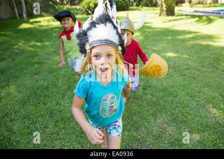 Drei Kinder tragen Fancy Dress Kostüme, spielen im park - Stockfoto