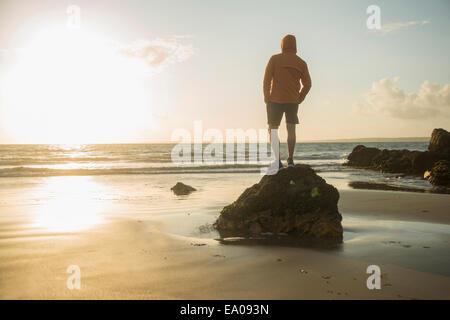 Reifer Mann, auf Felsen, Blick auf das Meer - Stockfoto