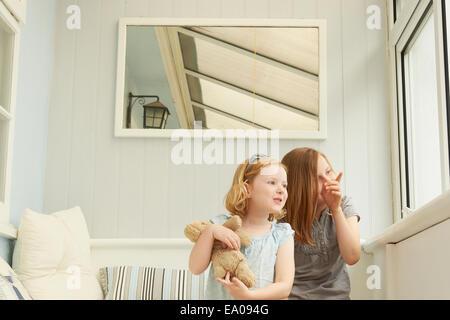 Zwei Schwestern zeigen und Blick aus Fenster Ferienwohnung - Stockfoto