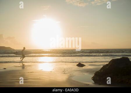 Reifer Mann, läuft in Richtung Meer, mit Surfbrett - Stockfoto