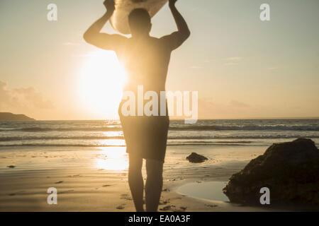 Reifer Mann, zu Fuß in Richtung Meer, mit Surfbrett - Stockfoto
