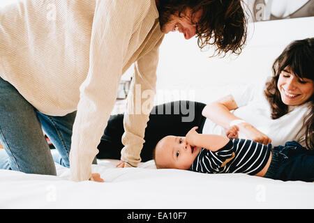 Eltern spielen mit Sohn auf Bett - Stockfoto