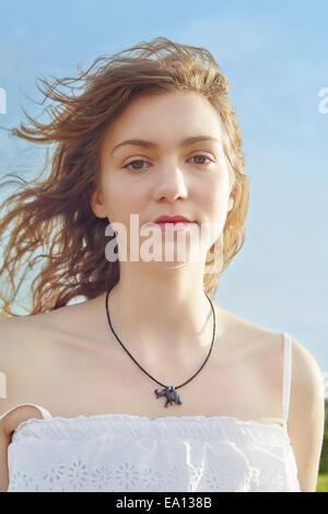Porträt der ruhige junge Frau mit Haaren im Wind wehen - Stockfoto
