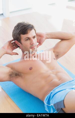 Bestimmt shirtless jungen Mann tut Sit Ups - Stockfoto