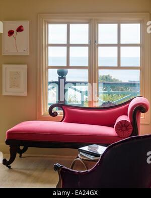 Englischer Regency rosa Chaiselongue im Schlafzimmer mit Louise Bourgeois Blume Bild und Meerblick - Stockfoto