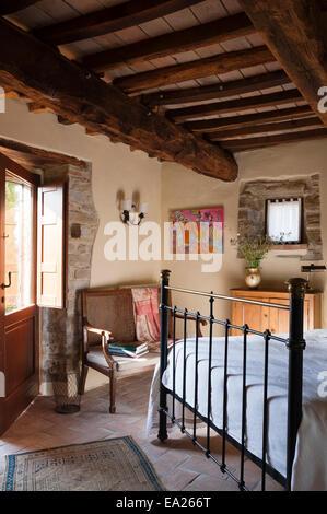 Eisen gerahmten Bett in rustikale Schlafzimmer mit Balkendecke und hellen Kunstwerk - Stockfoto