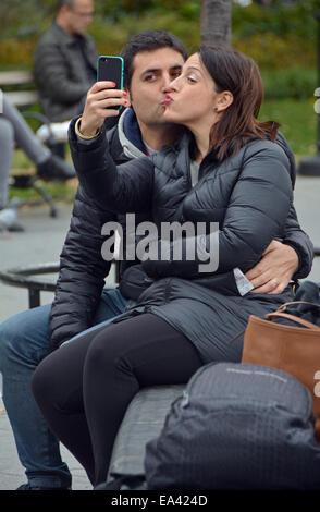 Ein paar küssen, wobei ein Selbstporträt im Washington Square Park in Greenwich Village, Manhattan, New York City - Stockfoto