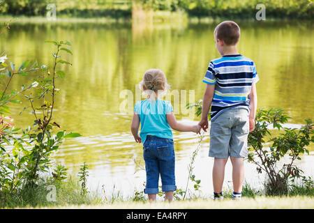 Älterer Bruder zeigen, ist Schwester des Sees und hielt ihre Hand für Sicherheit; Edmonton, Alberta, Kanada - Stockfoto