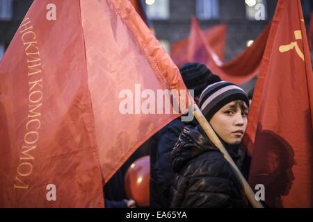 Nowosibirsk, Russland. 7. November 2014. Ein kleiner Junge trägt eine rote Fahne, wie er an einer Kundgebung des - Stockfoto