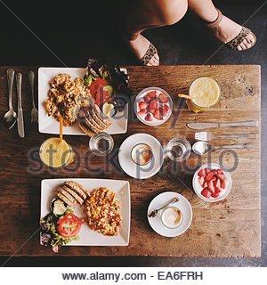 Draufsicht auf die Beine und Frau Frühstückstisch - Stockfoto