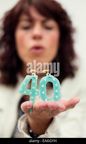 Frau, die Kerzen ausblasen, zum 40. Geburtstag - Stockfoto