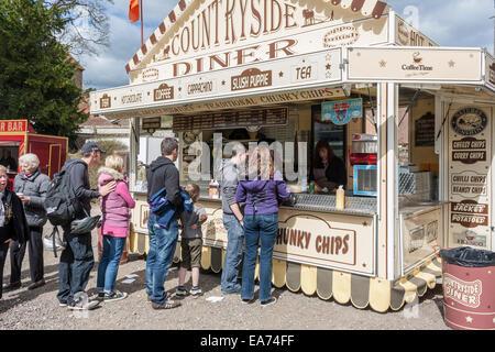 Nehmen Sie stand auf einem fairen Verkauf von Sommer-chips und Getränke zu Warteschlangen Kunden mit. - Stockfoto