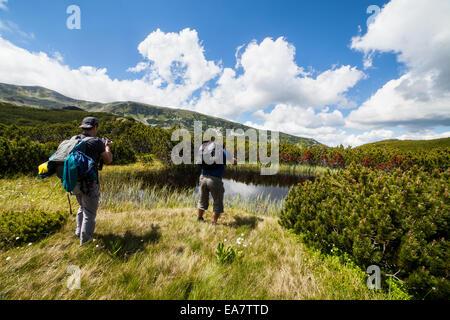 Zwei kaukasische Wanderer mit Rucksack wandern rund um einen See in den Bergen - Stockfoto