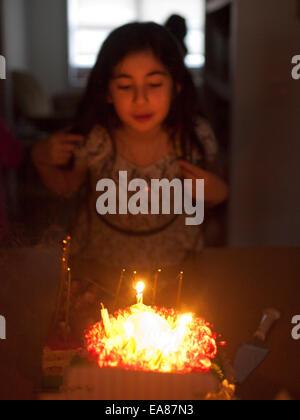 Junge Mädchen zu Hause Ausblasen der Kerzen auf einem Geburtstagskuchen. - Stockfoto