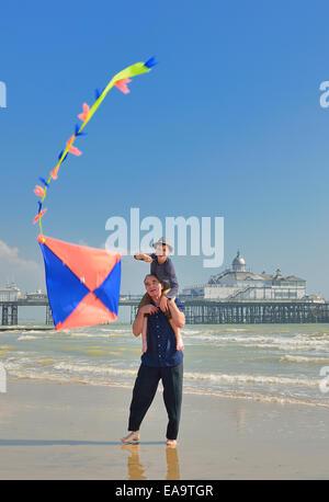Großvater mit Enkel fliegen einen Kite am Strand von Eastbourne. East Sussex. UK - Stockfoto
