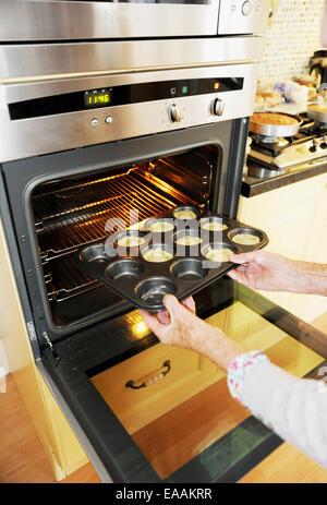 Ältere Frau Rentner Mince Pies zu Hause in ihrer Küche zu Weihnachten backen. Setzen sie in den Ofen - Stockfoto