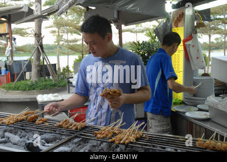 Mann Kochen Satay an Satay By The Bay Food-Center, Marina Bay, Singapur. - Stockfoto