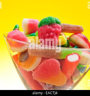 Nahaufnahme von einem Haufen von verschiedene Süßigkeiten in einem Glas auf einem gelben Hintergrund - Stockfoto