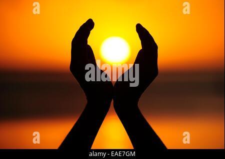 Zwei Hände halten die untergehende Sonne, La Gaulette, Mauritius - Stockfoto
