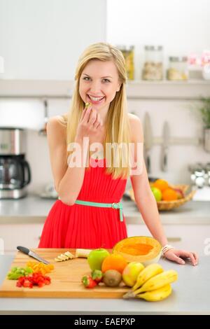 Glückliche junge Frau machen Obst Salat - Stockfoto